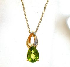 This is a beautiful 10K gold pear shaped green peridot pendant on a 10K gold chain. The genuine peridot gemstone is .7 carats and it topped by a small diamond. Both the pendant and chain are marked 10K and have a total weight of 1.2 grams.
