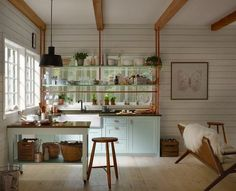 Small blue and white farmhouse kitchen boasts white shiplap walls accented with wood ceiling beams and a black pendant hung over a wood top white freestanding island placed against a wall under a window. White Farmhouse Kitchens, Cottage Kitchens, Small Kitchens, Bungalow Kitchen, Beach Kitchens, Dream Kitchens, Country Kitchen, Cute Kitchen, Kitchen And Bath