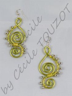 Boucles d'oreilles en fil aluminium vertes et grises. Composée de perles de rocaille grises et de crochets argentés. Ces boucles sont très légères et se porteront aisément en toute occasion. Facile à assortir à différents styles vestimentaires.