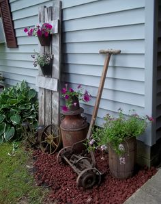 love old, rusty and unexpected pieces in the garden.. primitive milk can, barrel, old mower and especially love the flowers hanging off the shutter