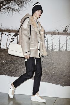 A look from the #CoachMens2015 presentation: the Stone Shearling Utility Jacket, Stone Suede Jean Jacket, Grey Heather/Grass Plastisol Graphic T-Shirt, Black Wool Trousers, Black/White Ribbed Beanie with Stripe, Feather Necklace, Black Cord Key, Shearling Turnlock Lo-Top Hiker and National Pebbled Small Manhattan Messenger