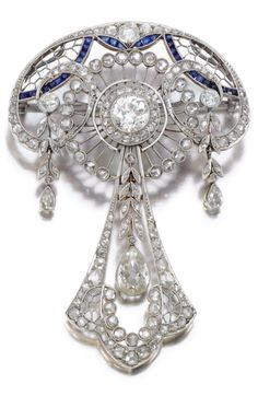 A BELLE EPOQUE SAPPHIRE AND DIAMOND BROOCH/PENDANT, CIRCA 1915. Of openwork foliate design highlighted with calibré-cut sapphires, centring on a circular-cut diamond within borders of cushion-shaped, circular-cut and rose diamonds, suspending three pear-shaped diamond drops, chain detachable, length approximately 4.8cm. #BelleÉpoque #brooch #pendant