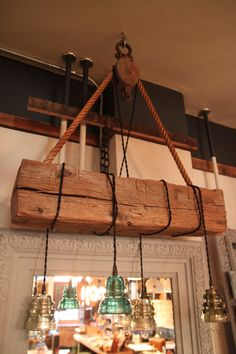 Hand hewn barn beam with hanging vintage insulators. Vintage Insulators have Edison bulbs lighting them hanging from the beam by vintage twisted cord. Holding the chandelier up is a reclaimed vintage pulley and rope from a local barn.