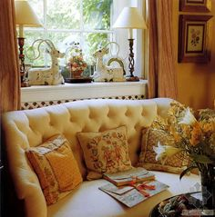 English vignette matching candlestick lamps in window tufted small sofa embroidered pillows window