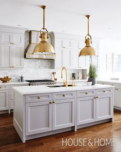 A stainless steel range hood trimmed in brass, large brass pendants above the island and matching hardware give designer Allison Willson's kitchen a unified feel. | Photographer: Stacey Brandford