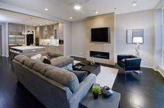 This is an open space between the kitchen and family room. Everything is done in variations of grey. Medium grey walls, light grey cabinetry, and very dark grey hardwood floors. The linear electric fireplace is so sleek and clean looking. Perfect for those cozy winter nights.