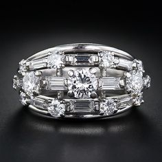 Oscar Heyman Platinum and Diamond Ring. chic and dazzling jewel, circa 1950s-1960s, is composed of twelve high-quality round brilliant-cut diamonds and ten straight baguette diamonds - totaling 2.50 carats.