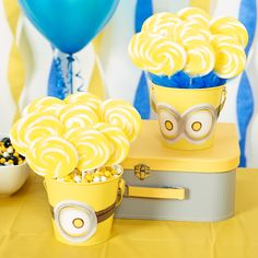 Mini metal buckets pre-painted in the proper shade of Minion yellow are the base of these adorable D.I.Y. Minions centerpieces. Paper Minion goggles give them the right look--just secure with a piece of tape in the back. Inside the buckets, we placed pieces of Styrofoam and stuck lollipop sticks inside. Finish by disguising the base of the bucket with some blue tulle fabric or using even more candy! To add texture & height, raise your centerpieces with varying levels of boxes or books.