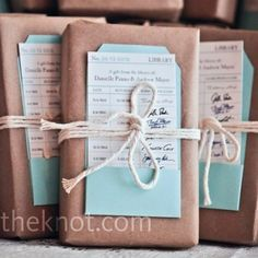 Book favors wrapped in brown paper, tied with twine, and a library checkout card used as a message