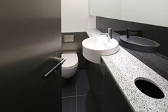 Natural stone vanities featuring inset wastebins