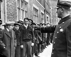 A Chicago police officer patrols a line of job seekers at a Humboldt Park registration station in 1933.