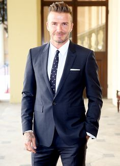 David Beckham look picture-perfect while wearing a navy suit with pleated pants, white shirt, and blue tie with white polka dots at Buckingham Palace.
