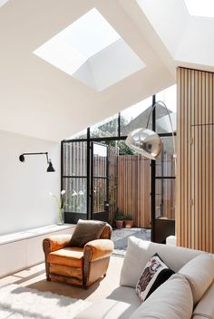 Bright modern living room with skylights and a minimalistic yet elegant decor.