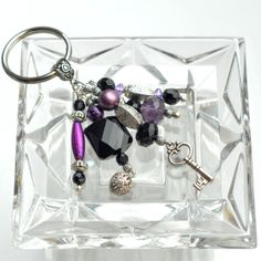 Purple Black and Silver Beaded Metal Key Fob by MOOREThanWood, $12.50. -->This purple, black and silver beaded metal key fob has an element of elegance and beauty. The key fob has a series of five beaded dangles in varied but themed patterns and shades of purple, black and silver. The dangles hang from a silver-tone, decorative metal bail. A silver-tone key charm and a filigree silver-tone ball charm give a little more dazzle to this great key chain.