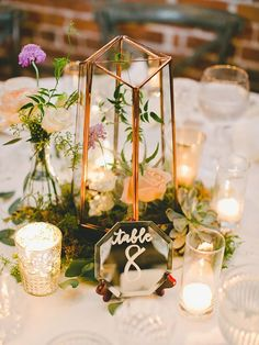A patch of moss, a romantic terreriam, candles, a few blooms and a succulent or two and you have a perfectly rustic tablescape as your wedding centerpiece decorations.