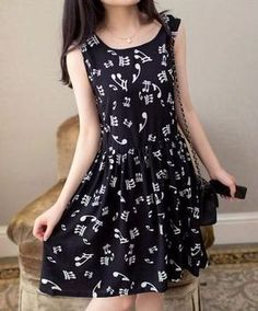 Black dress with white musical notes on it. It includes a gathered waist with a black zipper.