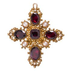 Victorian Granulated Garnet and Pearl Cross. An abundance of extremely fine granulation, rendered in high carat gold and highlighted with genets and pearls. For she who seeks a cross with a bit of character! The back is fitted with a pin-back and a bale- wear it as a brooch or a pendant. 2 inches by 1.75 inches, c 1890