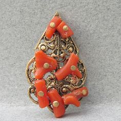 This very pretty small and delicate antique pendant from the late 1800's - early 1900's is made of filigree brass with small pieces of branch coral.