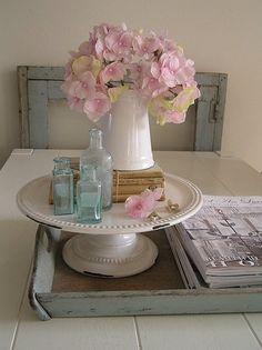 Vignette -- tray, cake plate, bottles, books. Hydrangeas in pitcher.