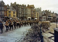 American troops march through the streets of a British port town on their way to the docks where they will be loaded into landing craft for the D-Day assault in June of 1944. (U.S. Army Photo)