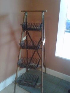 wire baskets attached to an old ladder for display- cute!