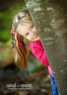 Three year old girl peeking from behind a tree, by Canonsburg PA photographer Pam Nafziger of Casual Moments Photography
