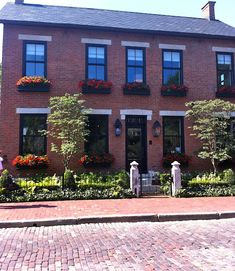 Black trim on red brick, black window boxes - via Hazardous Design. Black boxes RED flowers, green shrubbery.White flowers would work too.
