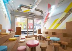 Bubble tea drinkers perch on tiers of cork seating in this brightly coloured London cafe by architects Gundry & Ducker.
