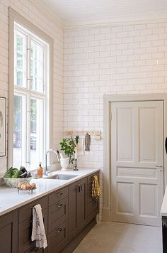 Floor to ceiling subway tile. Large windows. Bottom cabinets only. Oversize Hex Floor tiles