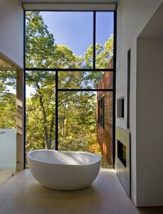 A contemporary bathroom, designed by architect Robert Gurney, features a free.standing tub, a fireplace inset into the wall, and an incredible wall of windows with a fabulous view.
