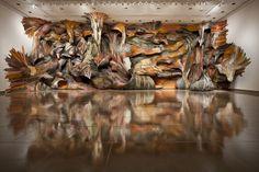Henrique Oliveira es un artista brasileño que vive en Sao Paulo que se inspira en la naturaleza. Sus grandes composiciones integran el espacio con la naturaleza mastodóntica que él imagina. Tal y como él entiende el arte, su obra cumple con el principal requisito: el impacto. Y el impacto, según él, no tiene nada que ver con la belleza. Con plástico, metal y resinas, construye el armazón de su escultura, que después recubre de diferentes clases de madera.