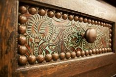 Embossed leather drawer front with nail head edging