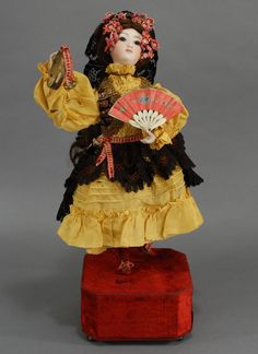 """Magnificent Roullet & Decamps Automaton """"Spanish Dancer"""" featuring a figure of a lady in all original attire, and with an exceptionally beautiful, rare, brown-eyed version of a seldom found portrait Jumeau bisque head (hairline from crown rim) and with bisque hands in perfect condition. Wind the mechanism, pull the stop and music begins as the dancer raises and lowers her left leg, she shakes her tambourine as bells tinkle and her head sways from side to side."""