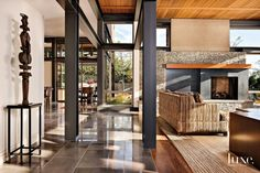 Warm, earthy elements, such as a massive stacked-stone fireplace with an oil-rubbed bronze surround and gray limestone flooring from Statements Tile, predominate in a Mercer Island home designed by architect Regan McClellan. The Cumaru-wood flooring in the living area is from Genesee Custom Floors & Interiors.