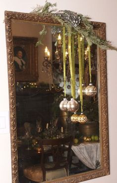 ornaments on ribbons with evergreen branch and pinecones sprayed silver draped over a mirror