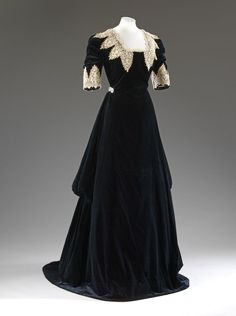 Evening dress of black silk velvet trimmed with white chemical lace in the Van Dyck manner, by John Redfern, c. 1909. The intentionally historical appearance of the gown suggests it may have been made for fancy dress. :copyright: Victoria and Albert Museum, London. See: http://collections.vam.ac.uk/item/O362559/evening-dress-john-redfern/