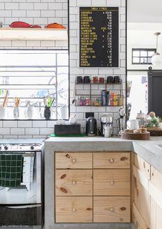 Cozinha integrada tem bancada de concreto, armário de pinus com puxadores de porcelana e subway tiles.