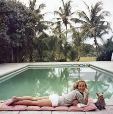 Socialite Alice Topping relaxing at a poolside in Palm Beach. A Wonderful Time - by Slim Aarons