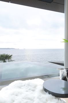 This modern home on the edge of the ocean features views from the living room and pool. Clean and minimal.