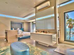 Bathroom: Bedroom With En‐Suite Bathroom And Vision Of South African Coast. ensuite bathroom. airy bedroom. metallic tufted bench. white vanity storage. floral rug. wood flooring. en-suite bathroom.