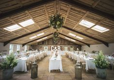 Long white tables stretch this countryside barn location, with elegant baskets of flowers hanging from above and big white light up letters pull the room together. For more inspiration visit www.weddingsite.co.uk