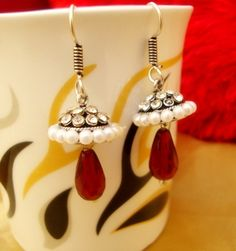 Trendy Earrings in jhumki style embedded with zircons and pearls with dangling red beads.