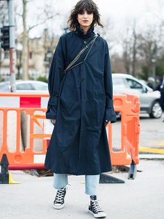 how to wear converse: long trench, jeans, and black high-tops with bold lipstick