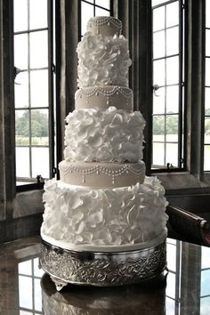 Wedding Cake Inspiration | A six tier white cake with intricate ruffle details and beading