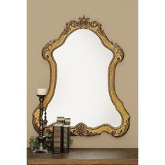 Finished in heavily-antiqued gold, this timeless wall mirror showcases traditional laurel leaf detail, intricately-carved trim, and a scarab-inspired finial.