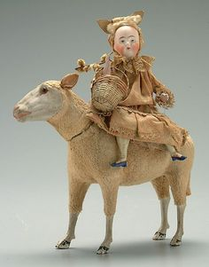 Antique Sheep Candy Container( head removes for candy) with an antique girl doll ,holding a basket, on it's back.