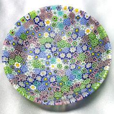 イタリア・ベネチアングラスのミルフィオーリです。このお皿の製造方法・過程はベネチアン紀行・モレッティーの技の中に撮影されています。同じようですがベネチアングラスは1点1点微妙に違ってくることが、おわかりいただけると思います。ベネチアングラスはベネチアングラスの趣き、クリスタルグラスはクリスタルのよさ、イスラム圏はイスラム圏の朴訥としたよさがあります。ミルフィオーリとはイタリア語で「1000の花」を意味します。その言葉通り、可憐な小花で埋め尽くされた お皿は、ベネチアのガラス職人が 何世紀も受け継いできた技を、今に伝えています。このシリーズは全て写真でご覧の箱ケースがついていますのでギフト向けになります。この会社のアイテムはネックレス、ミルフィオーリのペンダント、イヤリング等のアクセサリーとミルフィオーリのギフト用お皿を紹介、提供しています。輸入アクセサリー(欧米)は母の日、敬老の日、入学、卒園、お誕生日、クリスマス、にと大人対象のギフト向きです。イタリア製 ミルフィオーリ皿 (中) サイズ:直径105mm 深さ24mm程 材質:イタリア・ベネチアングラス