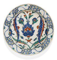 AN IZNIK POLYCHROME POTTERY DISH WITH LOTUS BLOSSOM AND SAZ LEAVES, TURKEY, SECOND HALF 16TH CENTURY decorated in cobalt blue, emerald green and relief red, featuring a lotus blossom with broken saz leaves, the border with wave-scroll pattern, foliate bud motifs to exterior, old collection label to underside 27cm. diam. Sotheby's
