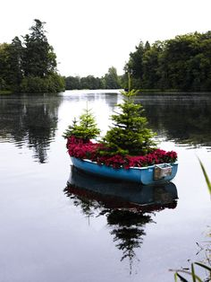 """IF I lived next to a lake AND had an old rustic boat, I'd """"shore"""" the boat at the edge of the lake, cut out the bottom of the boat, and let the plants take over naturally."""