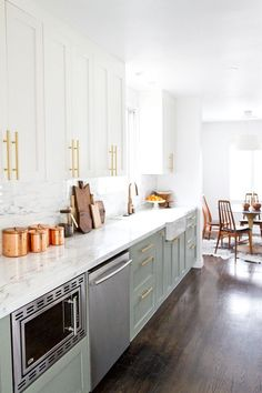 Obsessed with this kitchen and the gorgeous marble countertops! Love the mint cabinet color too.